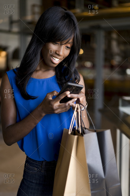 Female Afro-American using smartphone during shopping