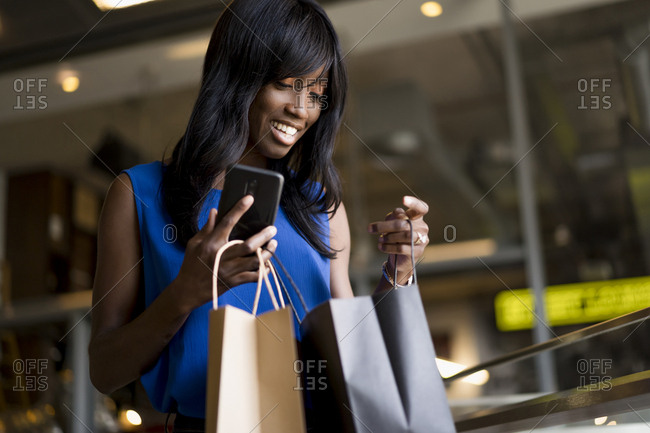 Female Afro-American holding smartphone during shopping
