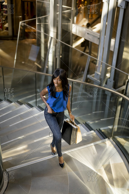 Female Afro-American with shopping bags in a mall- climbing stairs
