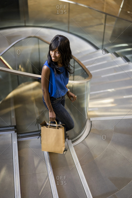 Female Afro-American with shopping bags in a mall- on steps