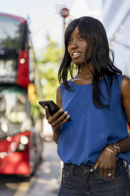 Female Afro-American using smartphone at bus stop in London- United Kingdom