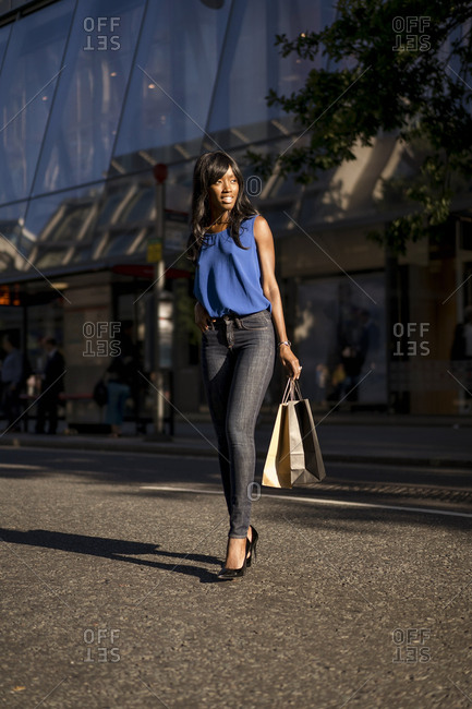 Female Afro-American with shopping bags looking sideways