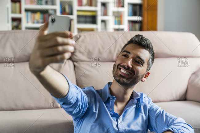 Portrait of smiling young man sitting in front of couch at home taking selfie with cell phone