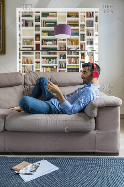 Smiling young man lying on the couch at home using smartphone and wireless headphones