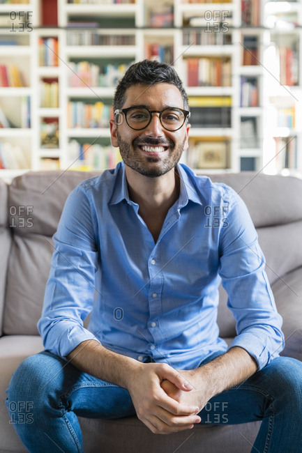 Portrait of happy young man sitting on the couch at home