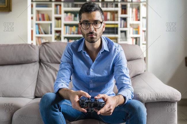 Portrait of serious young man sitting on the couch at home playing video game