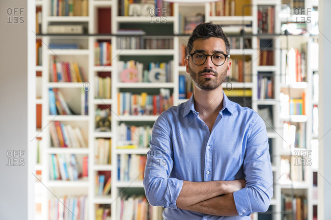 Portrait of bearded young man standing in front of bookshelves at home