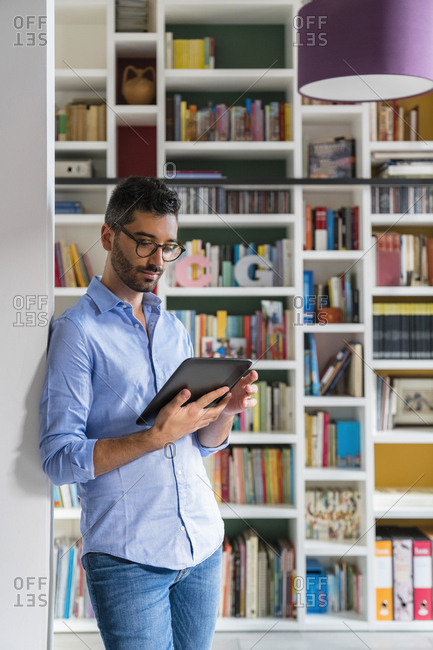 Portrait of young man standing in front of bookshelves at home using digital tablet