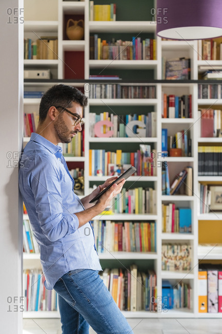 Young man standing in front of bookshelves at home using digital tablet