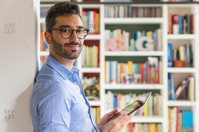 Portrait of smiling young man standing in front of bookshelves at home with digital tablet