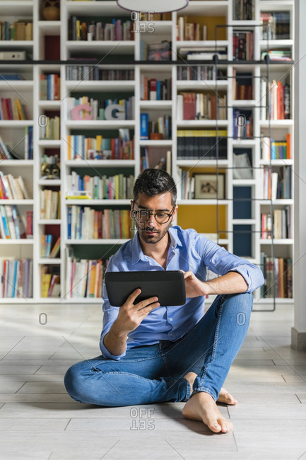 Portrait of barefoot young man sitting in front of bookshelves on the floor using digital tablet