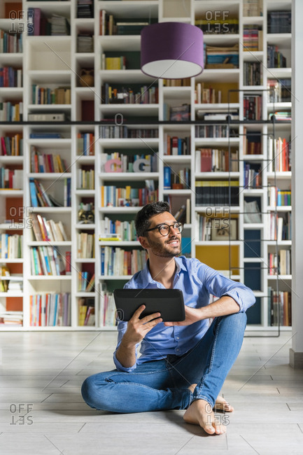 Portrait of barefoot young man sitting in front of bookshelves on the floor with digital tablet
