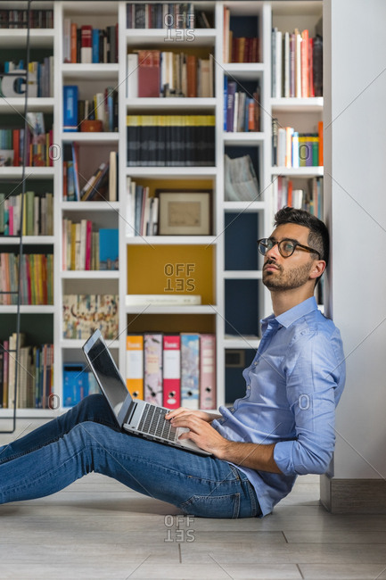 Portrait of pensive young man sitting in front of bookshelves on the floor using laptop