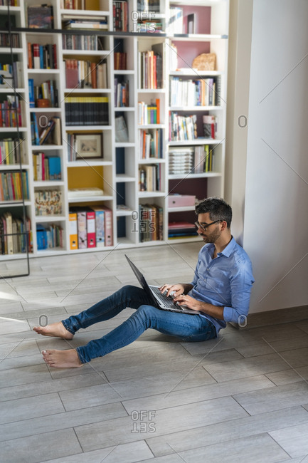 Barefoot young man sitting on the floor at home using laptop