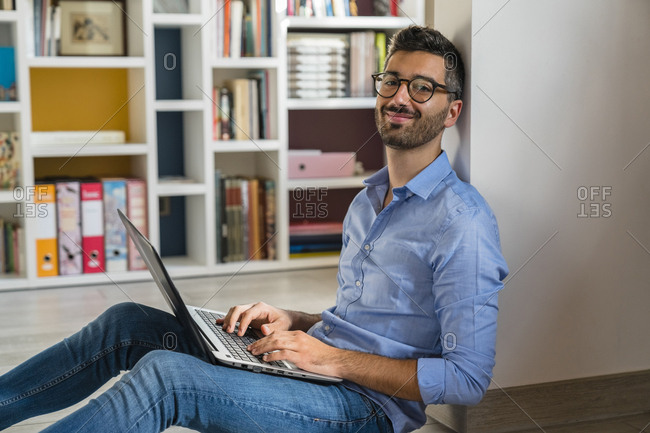 Portrait of smiling young man sitting on the floor at home using laptop