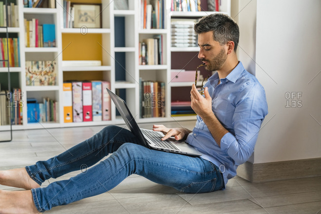 Young man sitting on the floor at home using laptop