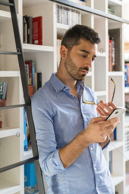 Portrait of pensive young man standing in front of bookshelf looking at cell phone