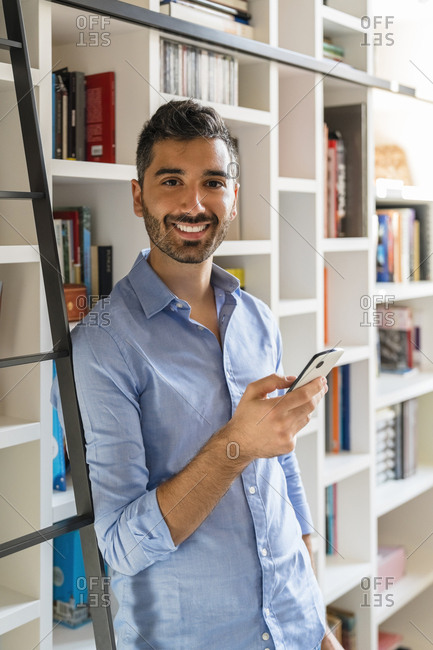 Portrait of smiling young man with smartphone standing in front of bookshelves at home