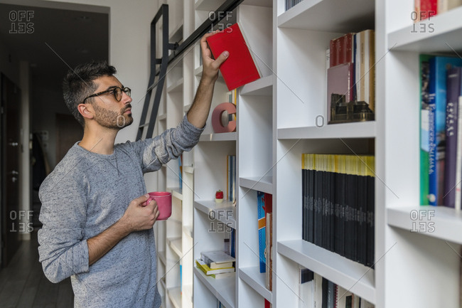 Portrait of young man with cup standing in front of bookshelves at home taking a book