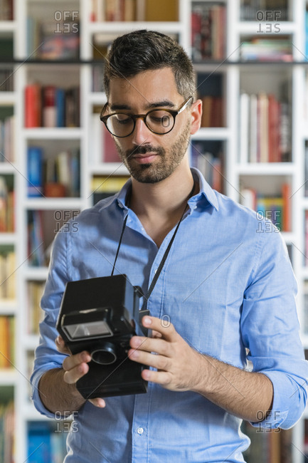 Portrait of young man standing in front of bookshelves looking at instant camera