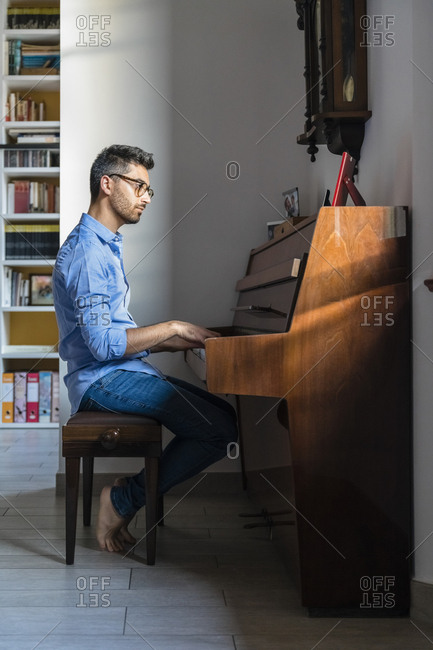 Barefoot young man playing piano at home