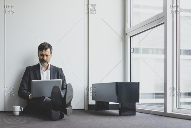 Mature businessman in office sitting on the floor using laptop