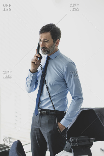 Serious mature businessman on the phone in office