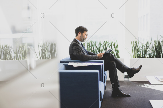 Mature businessman sitting in waiting area reading magazine