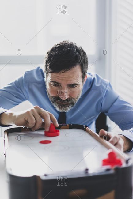 Mature businessman playing air hockey