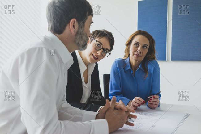 Businessman and two businesswomen working on plan on desk in office