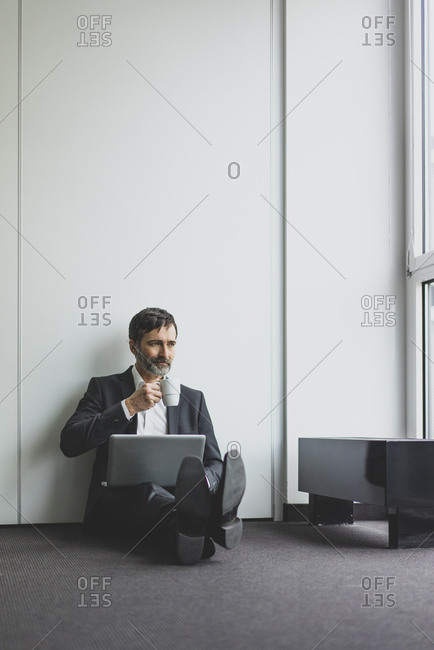 Mature businessman in office sitting on the floor with coffee cup and laptop