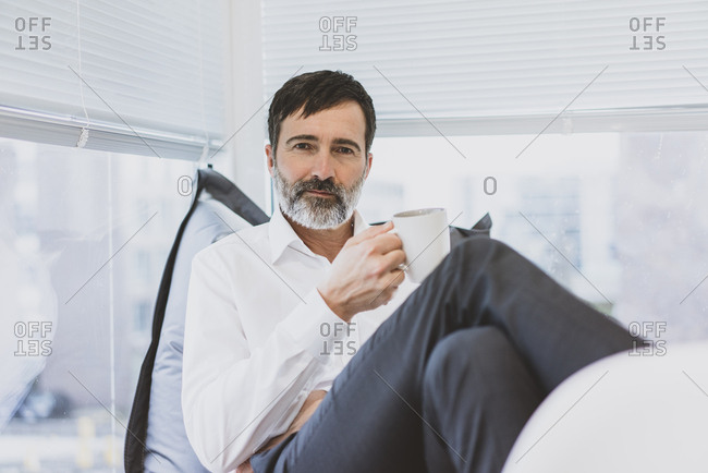 Portrait of mature businessman having a coffee break