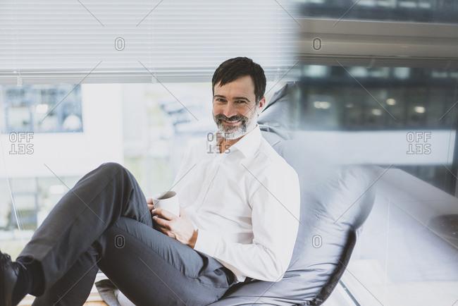 Portrait of smiling mature businessman having a coffee break