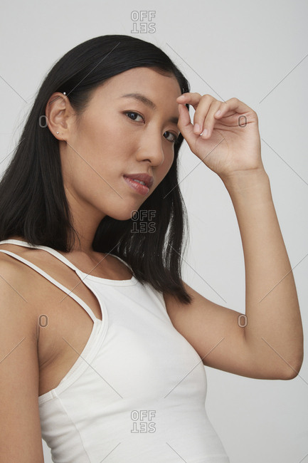 Portrait of young female Chinese woman- hand on forehead