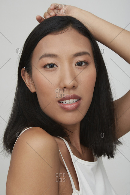 Portrait of young female Chinese woman- hand on head