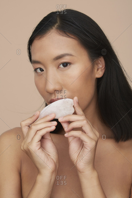 Portrait of young female Chinese woman using gua sha stone