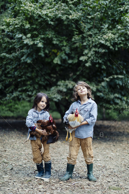 Two kids holding chickens on an organic farm