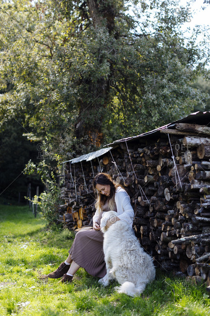 Pregnant woman with dog relaxing at stack of wood in garden