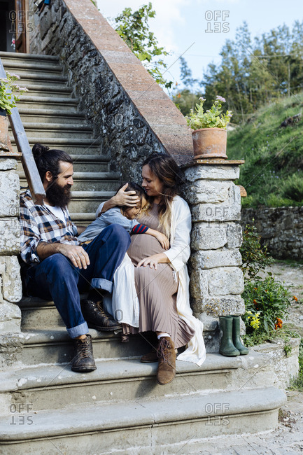 Family relaxing on stoop of a rustic house