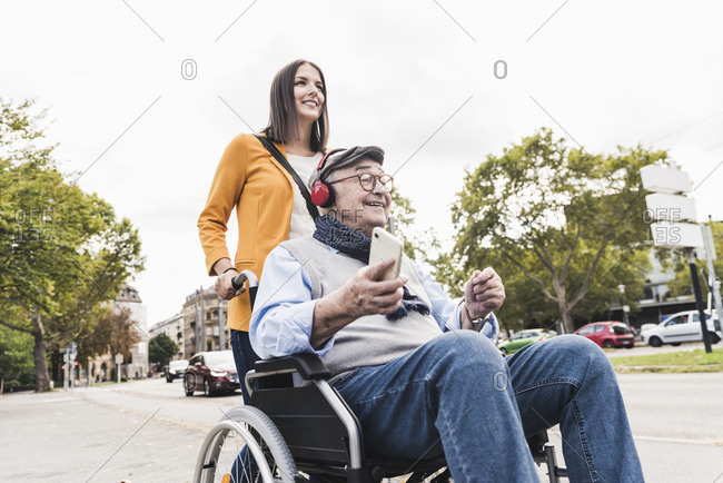 Young woman pushing senior man with headphones and smartphone in wheelchair