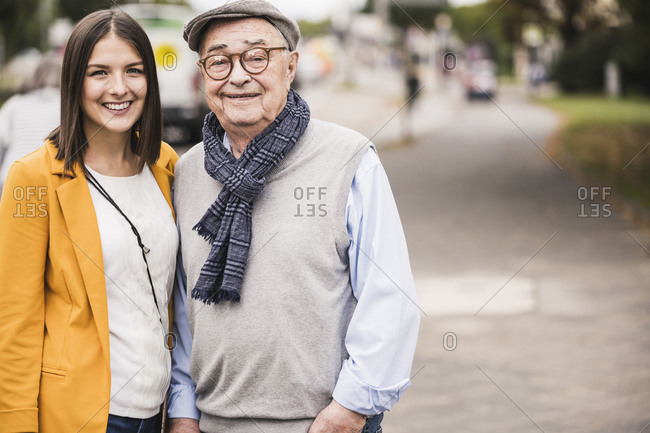 Portrait of senior man side by side with his adult granddaughter