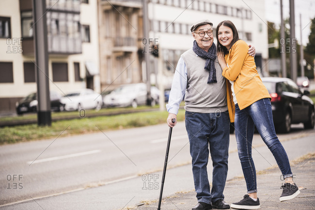 Portrait of happy senior man strolling with his adult granddaughter