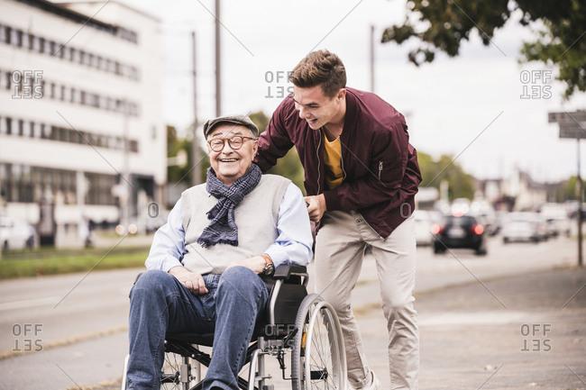 Young man pushing happy senior man in wheelchair