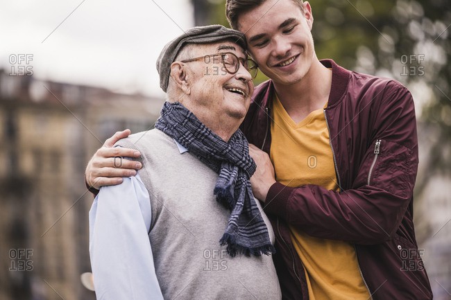 Happy senior man head to head with his adult grandson outdoors