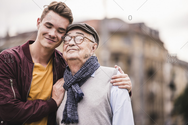 Portrait of happy senior man head to head with his adult grandson