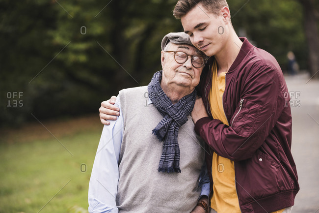 Portrait of senior man head to head with his adult grandson outdoors