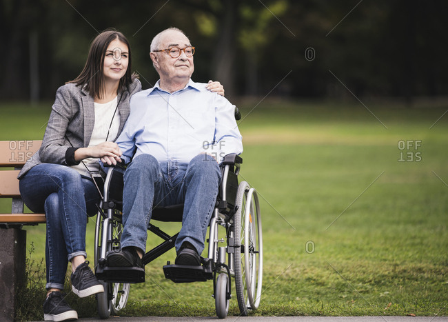 Portrait of senior man in a wheelchair relaxing with granddaughter in a park