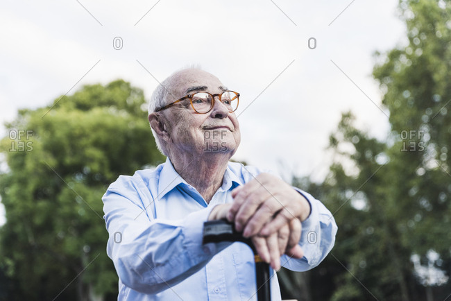 Portrait of senior man in a park leaning on his walking stick
