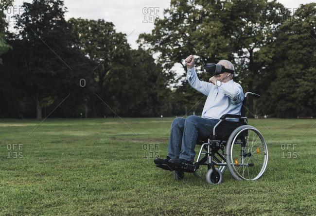 Senior man sitting in wheelchair using Virtual Reality Glasses