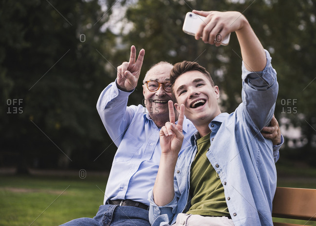 Senior man and grandson sitting together on a park bench taking selfie with smartphone